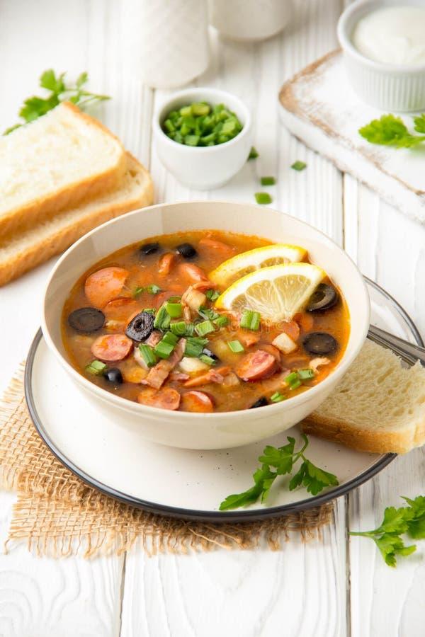 Soupe russe traditionnelle Solyanka avec du boeuf, le poulet, la saucisse, le citron, les olives et le concombre marin? D?jeuner  photo libre de droits