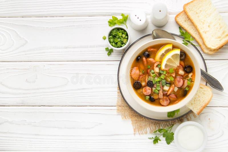 Soupe russe traditionnelle Solyanka avec du boeuf, le poulet, la saucisse, le citron, les olives et le concombre marin? D?jeuner  images stock