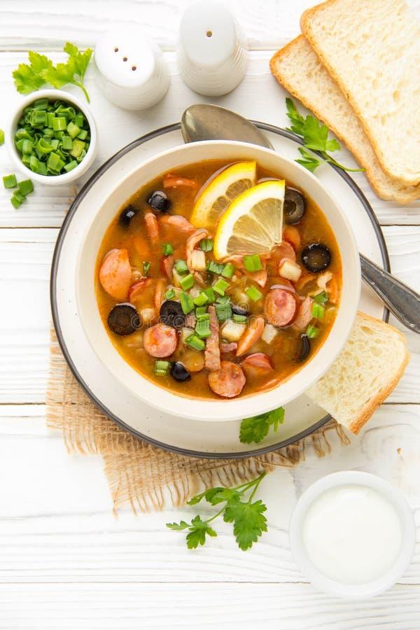 Soupe russe traditionnelle Solyanka avec du boeuf, le poulet, la saucisse, le citron, les olives et le concombre marin? D?jeuner  photos stock