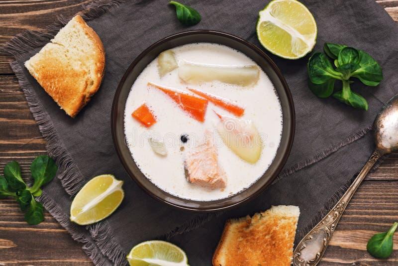Soupe scandinave et norvégienne à poissons sur un fond en bois rustique Soupe saumonée avec des pommes de terre, carottes, crème  images stock