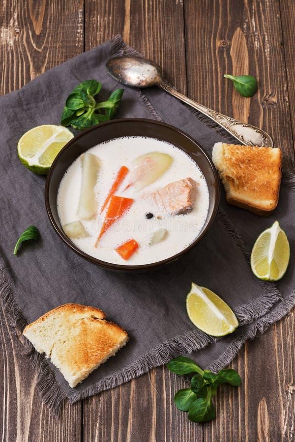 Soupe scandinave et norvégienne à poissons sur un fond en bois rustique Soupe saumonée avec des pommes de terre, carottes, crème  photo stock