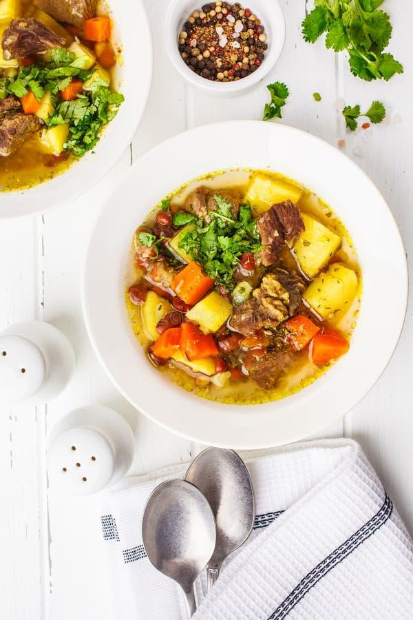 Soupe traditionnelle à eintopf avec de la viande, des haricots et des légumes dans un plat blanc, fond blanc image libre de droits