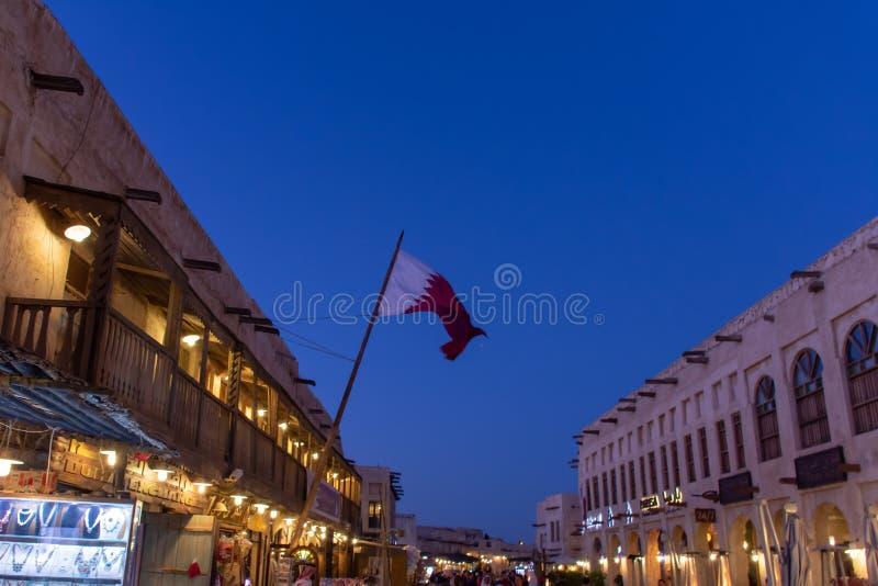 Souq Waqif på natten med en qatarisk flagga i Doha, Qatar i Mellanösten royaltyfri bild