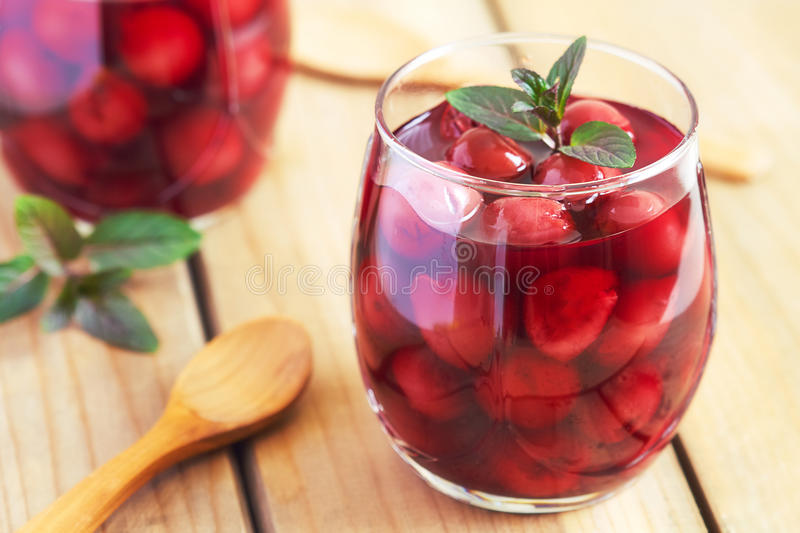 Sour cherry compote. Dessert served with mint leaves stock images