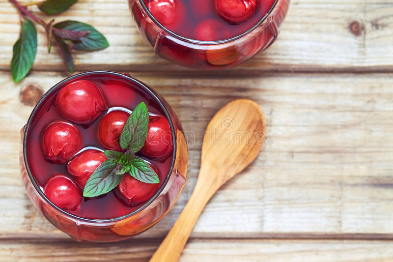 Sour cherry compote. Dessert served with mint leaves. Top view with copy space royalty free stock photos