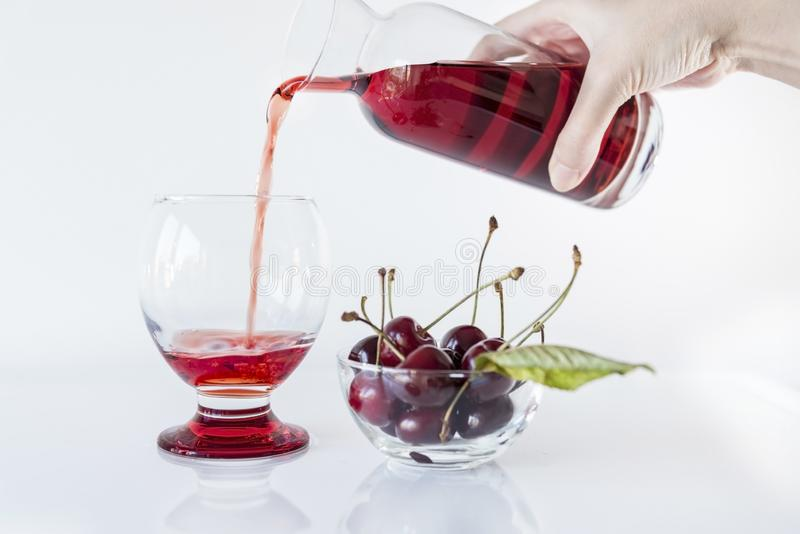 Sour cherry juice pouring into a glass on a white background with a bowl of sour cherry, close up royalty free stock photos