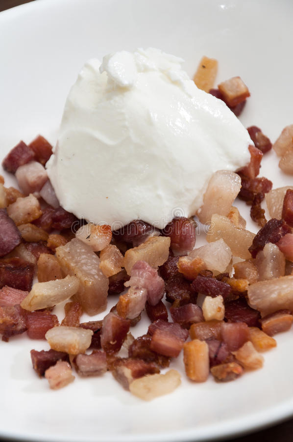 Sour cream on the fried sliced bacon stock images