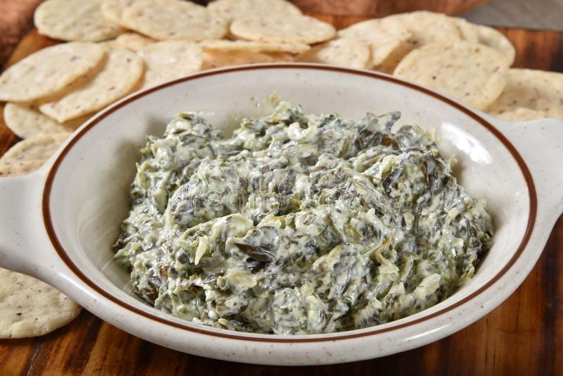 Sour cream & spinach dip with gluten free crackers royalty free stock image