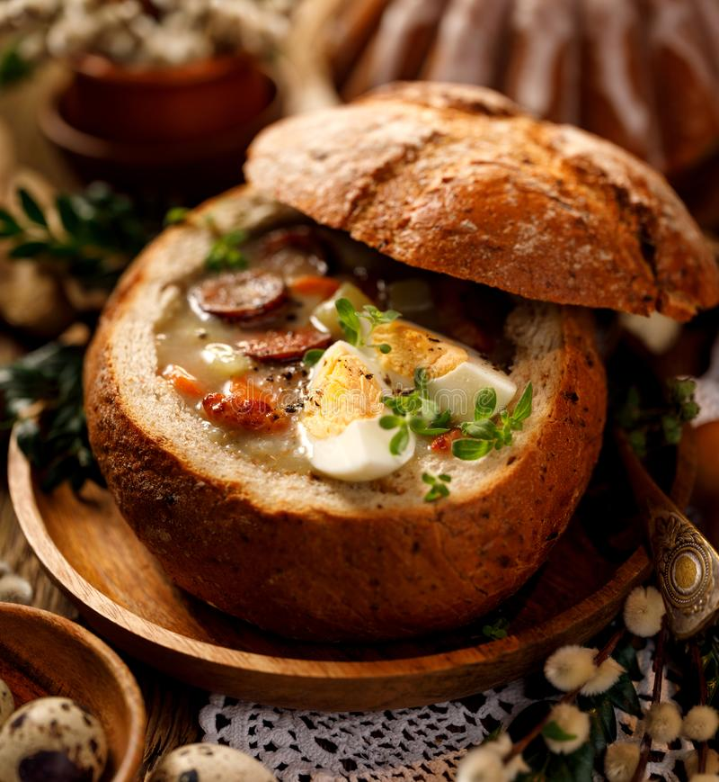 The sour soup Å»urek made of rye flour with smoked sausage and eggs served in bread bowl. royalty free stock photos
