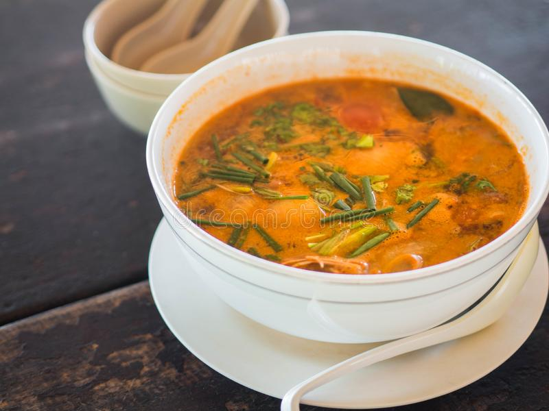 Sour and spicy Tom Yum Goong soup on a table in a restaurant. Thai traditional food. Authentic traditional Thai soup Tom Yam on a. Wooden table royalty free stock image