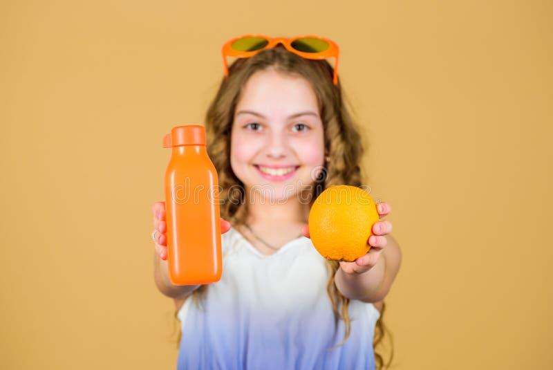 Source naturelle de vitamine La fille d'enfant mangent du fruit orange et boivent du jus d'orange Nutrition de vitamine Lunettes  photographie stock