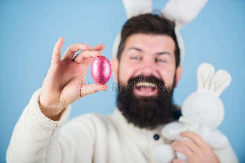 A source of new life. Hipster with long rabbit ears holding egg laying hare. Celebration of spring time holiday. Easter. A source of new life. Hipster with long stock photography