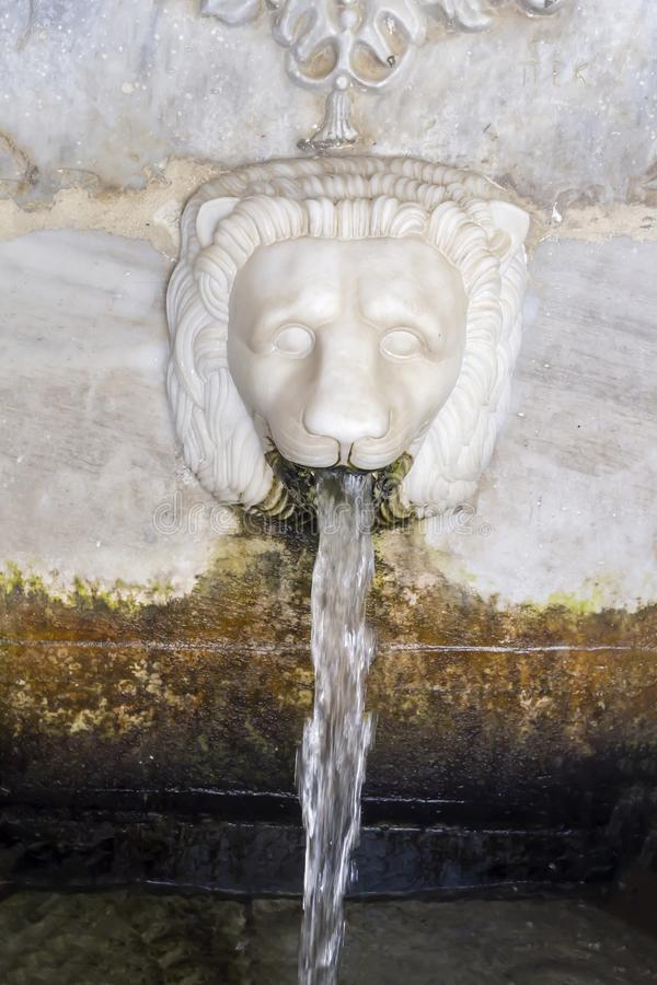 Source of Sariza with mineral water in the form of a lion`s head Andros island, Greece, Cyclades. A famous, marble source of Sariza with mineral, useful water in royalty free stock photo