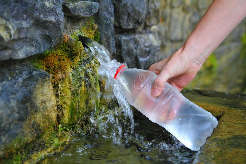 Source of spring water bottle filling holding hand. In Pyrenees mountain stock photos