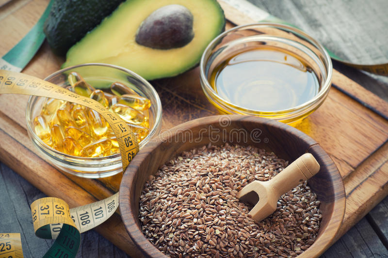 Sources of omega 3 fatty acids. Flaxseeds, avocado, oil capsules and flaxseed oil stock images