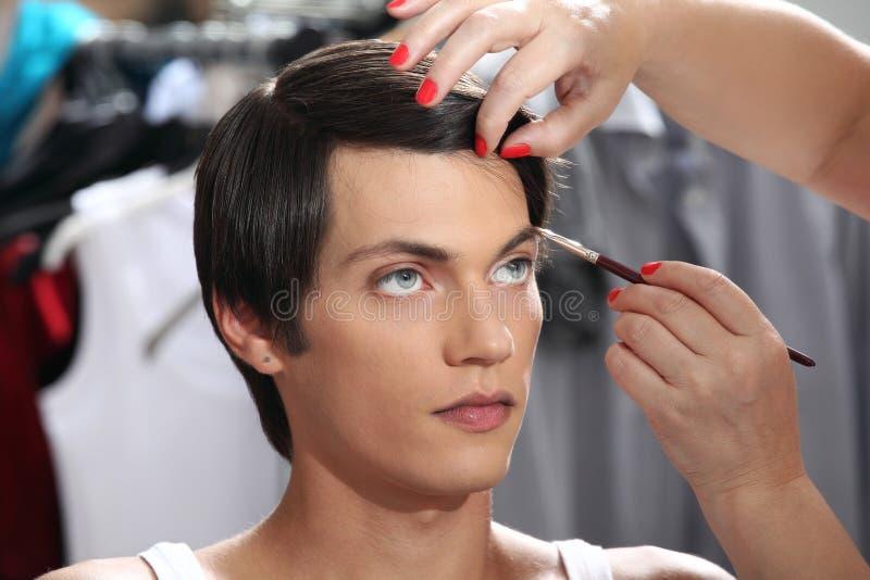 Sourcils avec la brosse de maquillage, modèle au miroir dans le vestiaire image stock