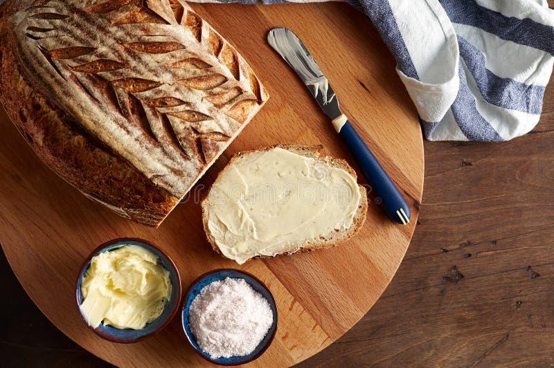 Sourdough ремесленника отрезал хлеб тоста с маслом и розовым гималайским солью на разделочной доске стоковое фото rf