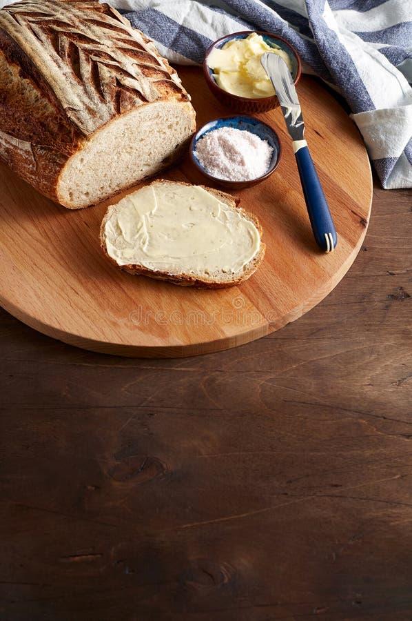 Sourdough ремесленника отрезал хлеб тоста с маслом и розовым гималайским солью на разделочной доске стоковые фотографии rf