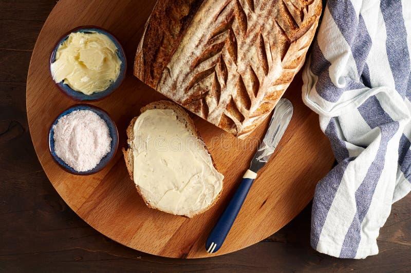 Sourdough ремесленника отрезал хлеб тоста с маслом и розовым гималайским солью на разделочной доске стоковые фото