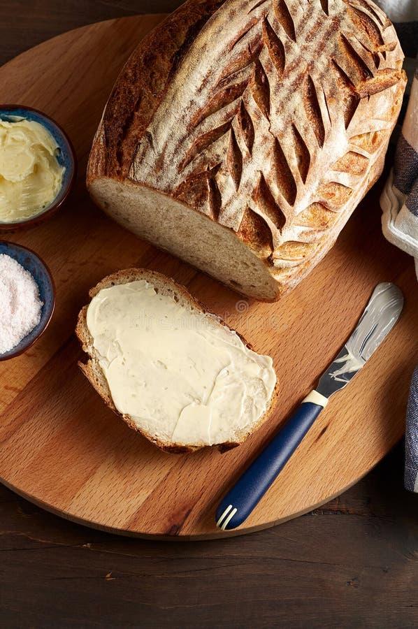 Sourdough ремесленника отрезал хлеб тоста с маслом и розовым гималайским солью на разделочной доске стоковое изображение rf
