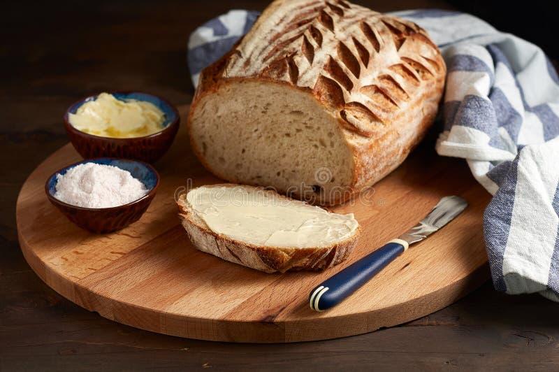 Sourdough ремесленника отрезал хлеб тоста с маслом и розовым гималайским солью на разделочной доске стоковое изображение