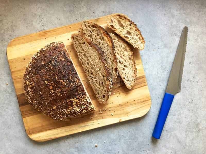 Sourdough artisanal chlebowi plasterki na drewnianej tnącej desce i bochenek fotografia stock