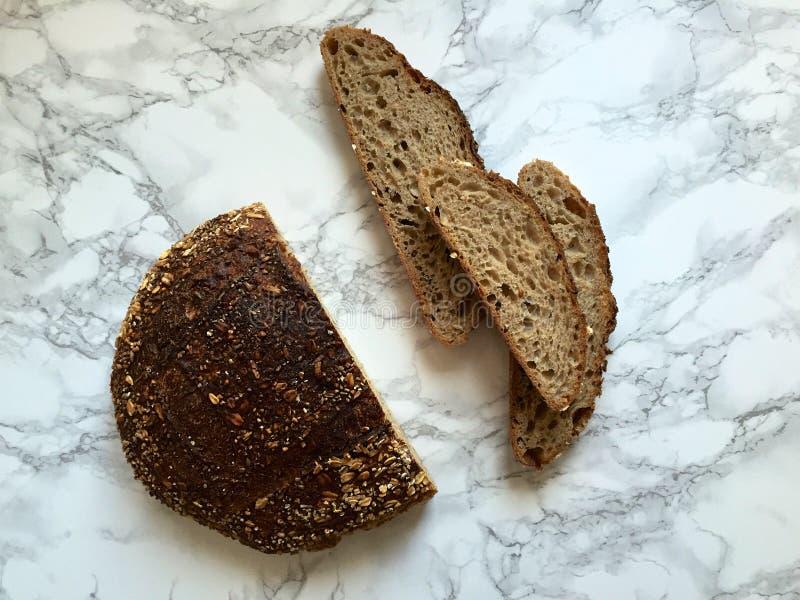 Sourdough artisanal chlebowi plasterki na marmurowym countertop i bochenek fotografia royalty free