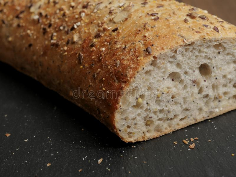 Sourdough bread, close up. On a dark slate plate. Fresh sourdough bread on a black slate plate on wooden table. Close up royalty free stock images