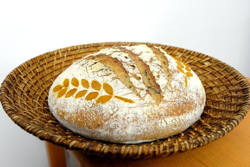 Sourdough chleb dekorował z pszeniczną pikantnością w koszu obraz royalty free