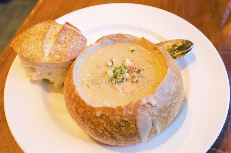 Sourdough Chowder. Close up of a Sourdough Chowder gourmet dish. A creamy soup made of clams and vegetables served in a loaf of bread by removing the top, a stock photo