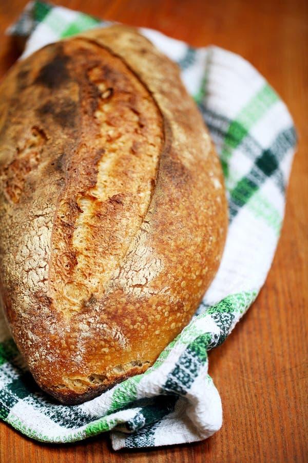 Sourdough släntrar bröd med ett snedstreck och den vresiga skorpan på en teatowel royaltyfri bild