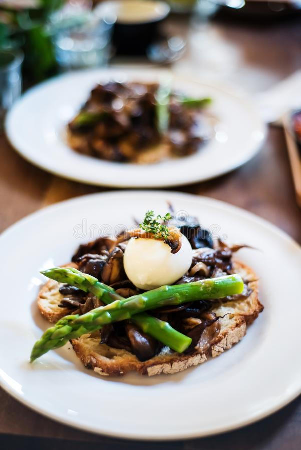 Sourdough toasted bread with mushrooms and asparagus. Sourdough toasted bread with three kind of mushrooms, poached egg and asparagus royalty free stock photos