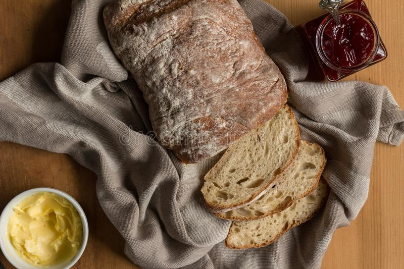 Sourdoughbröd släntrar på maträtthandduken med smör och driftstopp på den lantliga trätabellen royaltyfri foto