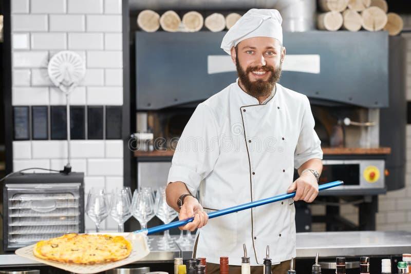 Souriant, boulanger heureux conservant la pizza, regardant l'appareil-photo image libre de droits