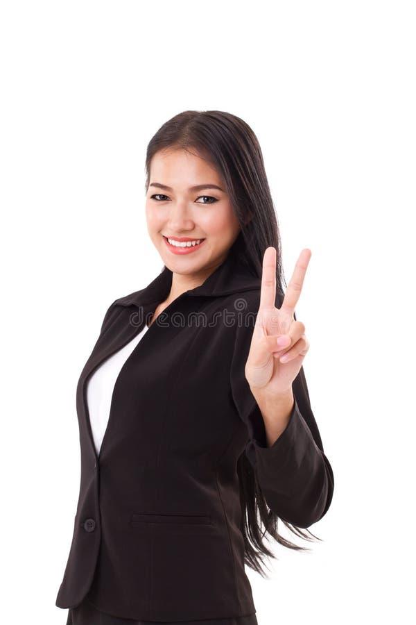 Souriant, cadre supérieur féminin sûr et réussi d'affaires montrant le signe de victoire de 2 doigts photos stock