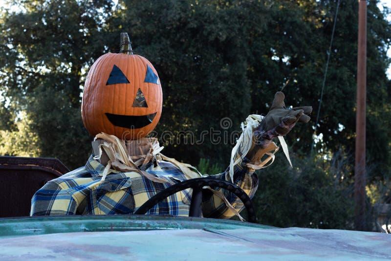 Souriant, heureux, accueillant, épouvantail amical de tête de potiron d'amusement conduisant un vieux camion à une partie de réco photos stock
