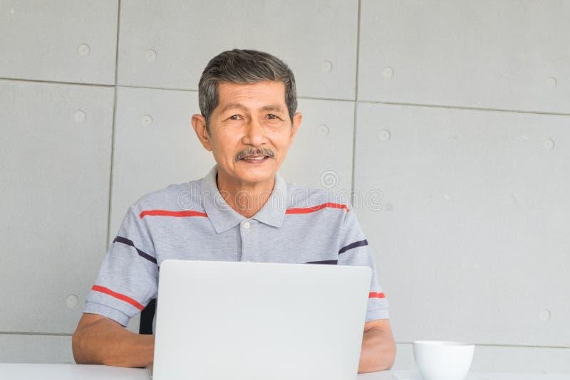 Souriant, homme sup?rieur asiatique Robe avec les v?tements sport se reposant et travaillant ? la table avec l'ordinateur portabl images libres de droits