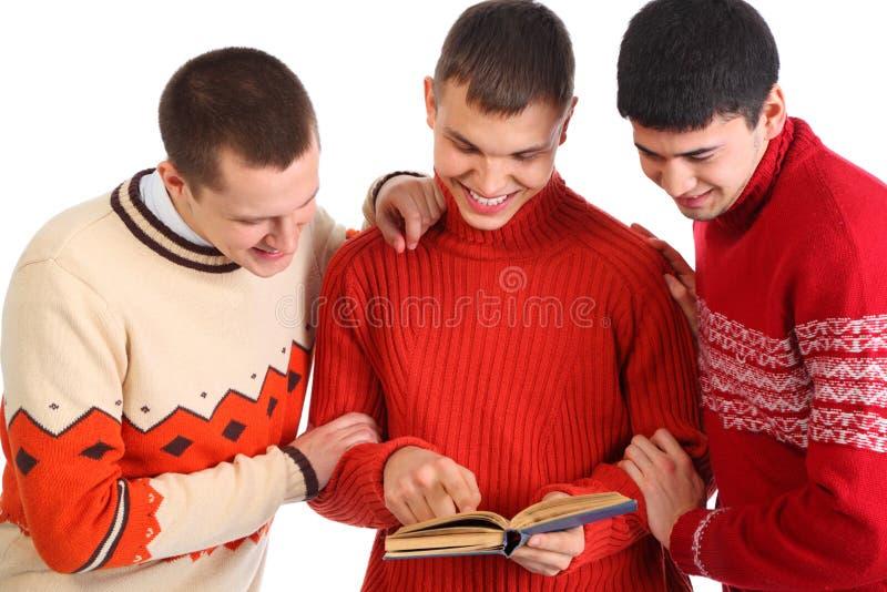 sourire affiché par hommes de livre trois jeunes photos stock