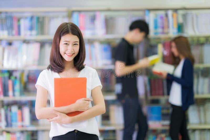 Sourire asiatique de dame d'étudiant et lu un livre dans la bibliothèque images stock