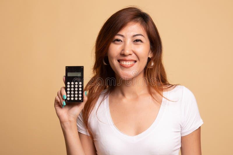 Sourire asiatique de femme avec la calculatrice photographie stock libre de droits