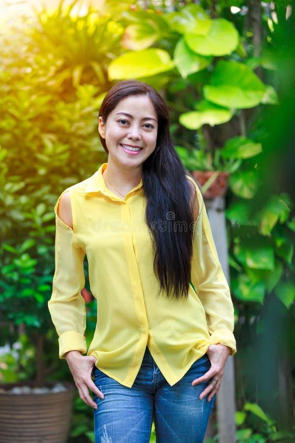 Sourire asiatique de femme heureux au parc Extérieur avec la lumière du soleil lumineuse photo libre de droits