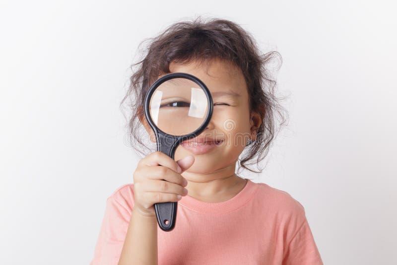 Sourire asiatique de loupe de participation de petite fille Une petite fille mignonne d'enfant regardant la loupe sur le fond bla image libre de droits