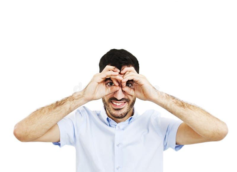 Sourire beau de jeune homme, faisant des jumelles avec ses mains image libre de droits