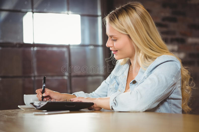 Sourire blond ayant le café et écrivant dans le planificateur photographie stock libre de droits