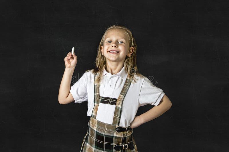 Sourire blond junior doux d'écolière heureux devant le tableau noir de salle de classe d'école photos libres de droits