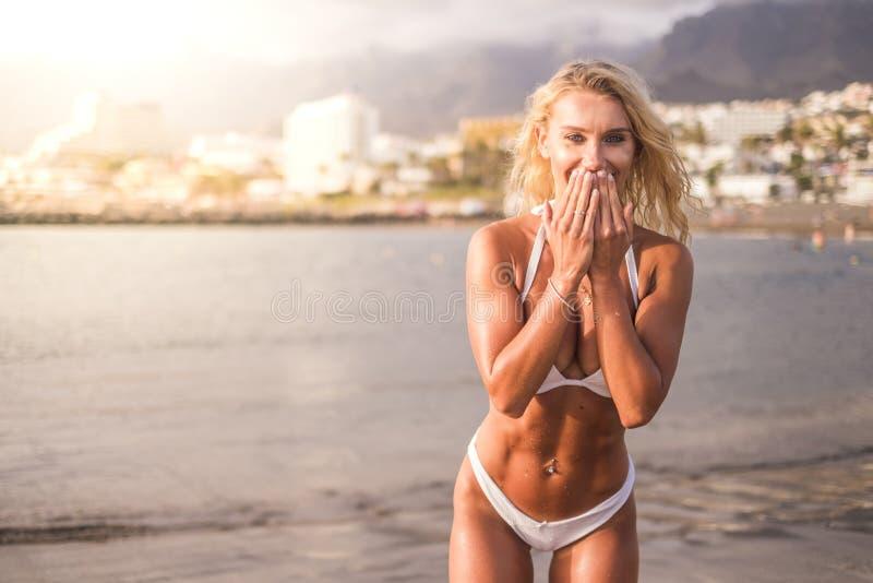 Sourire bronzé de corps de bébé et apprécier les vacances d'été envoyant des baisers fille parfaite de forme physique à la plage  photo libre de droits