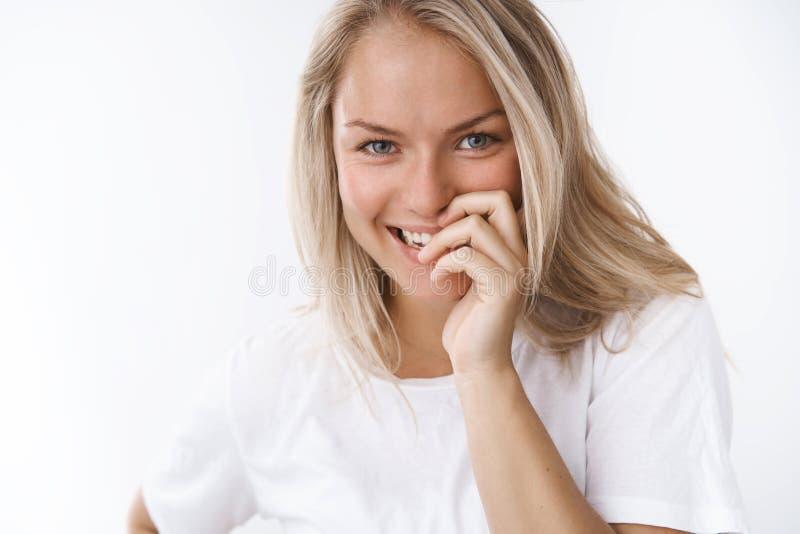 Sourire couvrant flirty riant nerveusement jeune d'amie blonde attirante douce et tendre avec des doigts regardant fixement la ca images libres de droits