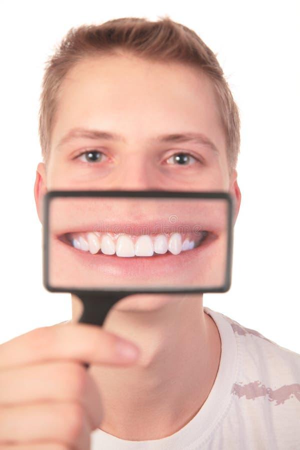Sourire d'expositions d'homme par la loupe photos stock
