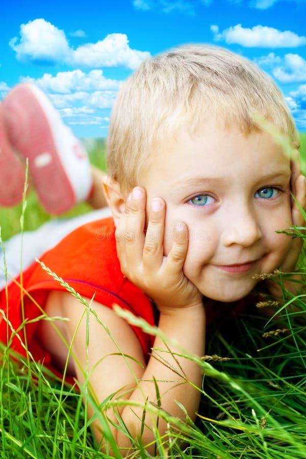 Sourire d'herbe mignonne heureuse d'enfant au printemps photos stock