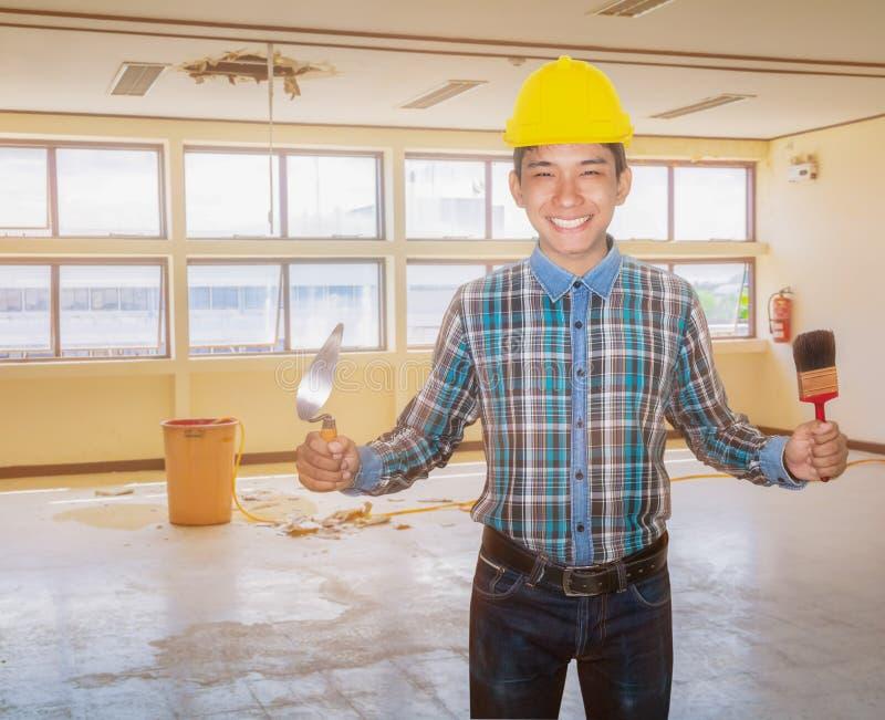 Sourire d'ingénieur avec le pinceau de truelle et de triangle de participation de main dans l'immeuble de bureaux int?rieur de ba images libres de droits